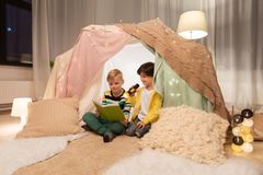 Happy boys reading book in kids tent at home. Childhood, hygge and friendship concept - happy boys reading book with torch light in kids tent or teepee at home Royalty Free Stock Images