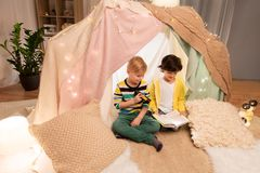Happy boys reading book in kids tent at home. Childhood, hygge and friendship concept - happy boys reading book with torch light in kids tent or teepee at home Stock Photo