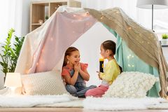 Girls playing with torch in kids tent at home. Childhood, hygge and friendship concept - happy girls playing with torch light in kids tent at home royalty free stock image