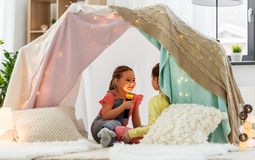 Girls playing with torch in kids tent at home. Childhood, hygge and friendship concept - happy girls playing with torch light in kids tent at home royalty free stock photo