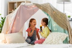 Girls playing with torch in kids tent at home. Childhood, hygge and friendship concept - happy girls playing with torch light in kids tent at home stock photography