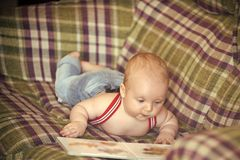 Childhood, infancy innocence. Knowledge, education, literature. Baby boy read book on sofa. Infant wear jeans and suspenders at home. Child development concept royalty free stock photography