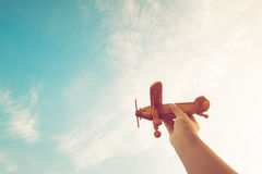 Childhood inspiration. Hands of children holding a toy plane and have dreams wants to be a pilot - Vintage filter effect Stock Images