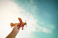 Childhood inspiration. Hands of children holding a toy plane and have dreams wants to be a pilot - Vintage filter effect Stock Photo