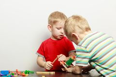 Two little boys playing with toys having fun stock images