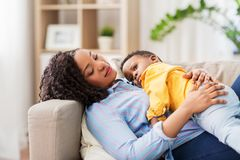 Happy african american mother with baby at home. Childhood, kids and people concept - happy african american mother with her baby son lying on sofa at home royalty free stock images
