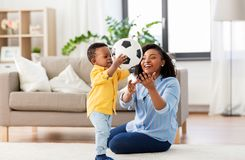 Mother and baby playing with soccer ball at home. Childhood, kids and people concept - happy african american mother and her baby son playing with soccer ball stock images
