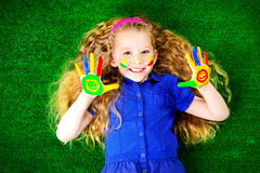 Childhood. Laughing little girl painted in bright colors lying on green grass. Happy childhood Royalty Free Stock Photo