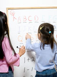 Childhood learning. Two young girls learning their numbers and letters Royalty Free Stock Photo
