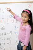 Childhood learning. A young girl learning her numbers and letters Stock Photo