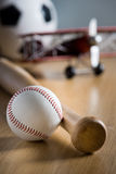 Childhood leisure activities. Baseball bat and hardball on wooden floor with toy plane and soccer ball on background Stock Photo