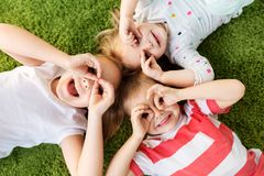 Happy little kids looking through finger glasses stock photos