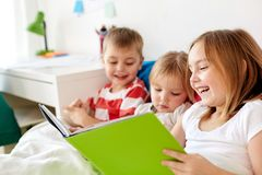 Little kids reading book in bed at home. Childhood, leisure and family concept - little kids reading book in bed at home Stock Photo