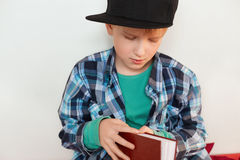 Childhood and leisure. Image of schoolboy in stylish checked shirt and cap opening red book isolated over white background wanting. To read interesting stories Royalty Free Stock Image