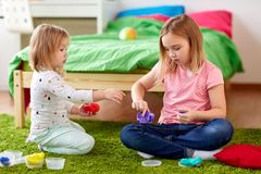 Sisters with modelling clay or slimes at home. Childhood, leisure and people concept - girls or sisters with modelling clay or slimes at home Royalty Free Stock Photos