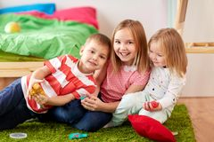 Kids with modelling clay or slimes at home. Childhood, leisure and people concept - group of kids with modelling clay or slimes at home Stock Photography