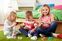Kids with modelling clay or slimes at home. Childhood, leisure and people concept - group of kids with modelling clay or slimes at home Stock Images