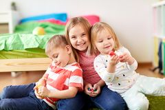 Kids with modelling clay or slimes at home. Childhood, leisure and people concept - group of kids with modelling clay or slimes at home Royalty Free Stock Photo
