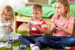 Kids with modelling clay or slimes at home. Childhood, leisure and people concept - group of kids with modelling clay or slimes at home Stock Image