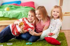 Kids with modelling clay or slimes at home. Childhood, leisure and people concept - group of kids with modelling clay or slimes at home Stock Photos