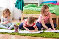 Happy kids drawing at home. Childhood, leisure and people concept - happy kids drawing and making crafts at home Stock Image