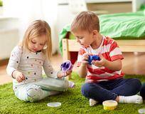Little kids with modelling clay or slimes at home. Childhood, leisure and people concept - little kids with modelling clay or slimes at home Royalty Free Stock Photography