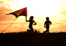Childhood memories. Two kids flying a kite at sunset invoke childhood memories Royalty Free Stock Photos