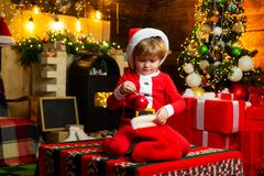 Childhood moments. Kid boy santa hold christmas gift red sock. Christmas stocking concept. Child cheerful face got gift. In christmas sock. Check contents of stock photo