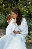 Childhood and Motherhood. Mother lovingly kisses her infant daughter on the cheek.  Both are in white dresses and are in a garden with flowers Stock Images