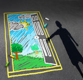 Childhood Opportunity. Concept and child imagination symbol as a shadow of a boy looking down on a pavement with a chalk drawing of an open door with a green Stock Photo