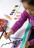 Childhood Painting 003. A young girl paints her masterpiece with bright colors Royalty Free Stock Photos
