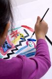 Childhood Painting 004. A young girl paints her masterpiece with bright colors Royalty Free Stock Image