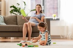 Happy baby girl playing with toy blocks at home stock photo