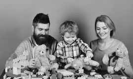 Childhood and playing concept. Mom, dad and kid in playroom. Man with beard, woman and boy play on green background. Family with curious faces hold teddy bears stock photo
