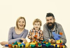 Childhood and playing concept. Mom, dad and kid in playroom. Man with beard, woman and boy play on white background. Childhood and playing concept. Mom, dad and stock photo