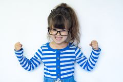 Childhood, power, gesture and people concept - happy smiling little girl with raised hand. Funny strong child with eye glasses stock photos