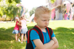 Childhood problems. Sad lonely child being bullied by children Stock Photo