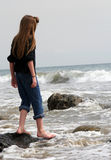 Childhood Reflections. Young girl looking out towards the Pacific Ocean royalty free stock photos