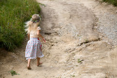 Childhood road. Little girl in wild flowers wreath walking barefoot on summer road royalty free stock photos