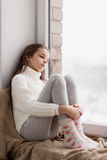 Sad girl sitting on sill at home window in winter Royalty Free Stock Photos