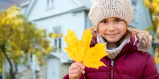 Close up of girl with autumn maple leaf over house. Childhood, season and real estate concept - close up of happy little girl with fallen maple leaf in autumn stock photos