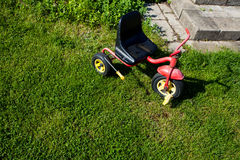 Childhood. Small red tricycle cycle toy on grass. Royalty Free Stock Image