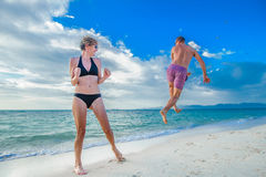 Childhood in the soul: a couple of thirty-year-olds jumping and. Remember the childhood: a couple of thirty-year-olds jumping and running along the beach Stock Photography