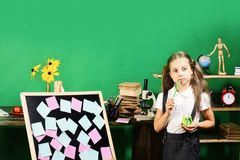 Childhood and study time concept. Girl holds green clock. And pencil by blackboard with pink and blue stickers. Schoolgirl with thoughtful face in classroom stock photos