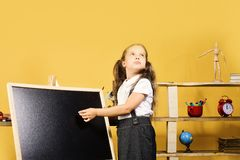 Childhood and study time concept. Schoolgirl with dreamy face. And ponytails stands in her classroom. Kid and school supplies on yellow wall background. Girl royalty free stock photos