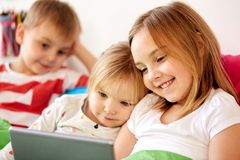 Happy little kids with tablet pc in bed at home. Childhood, technology and family concept - happy little kids with tablet pc computer in bed at home Royalty Free Stock Photos
