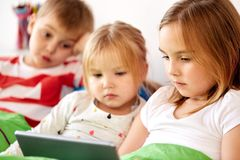 Little kids with tablet pc in bed at home Royalty Free Stock Photos