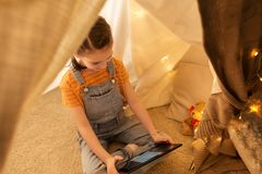 Little girl with tablet pc in kids tent at home. Childhood, technology and hygge concept - happy little girl with tablet pc computer in kids tent at home Royalty Free Stock Photography