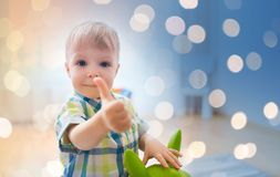 Happy baby boy playing with toy showing thumbs up. Childhood, toys and people concept - happy little baby boy playing with ride-on toy horse and showing thumbs Stock Photo