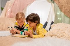 Boys with magnifier and map in kids tent at home. Childhood, travel and hygge concept - happy little boys with magnifier and road map searching location in kids royalty free stock photography